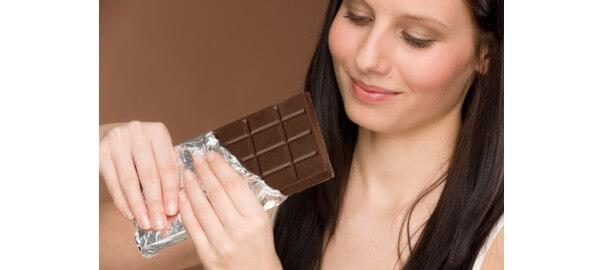 Dívka s chutí hledí na čokoládu